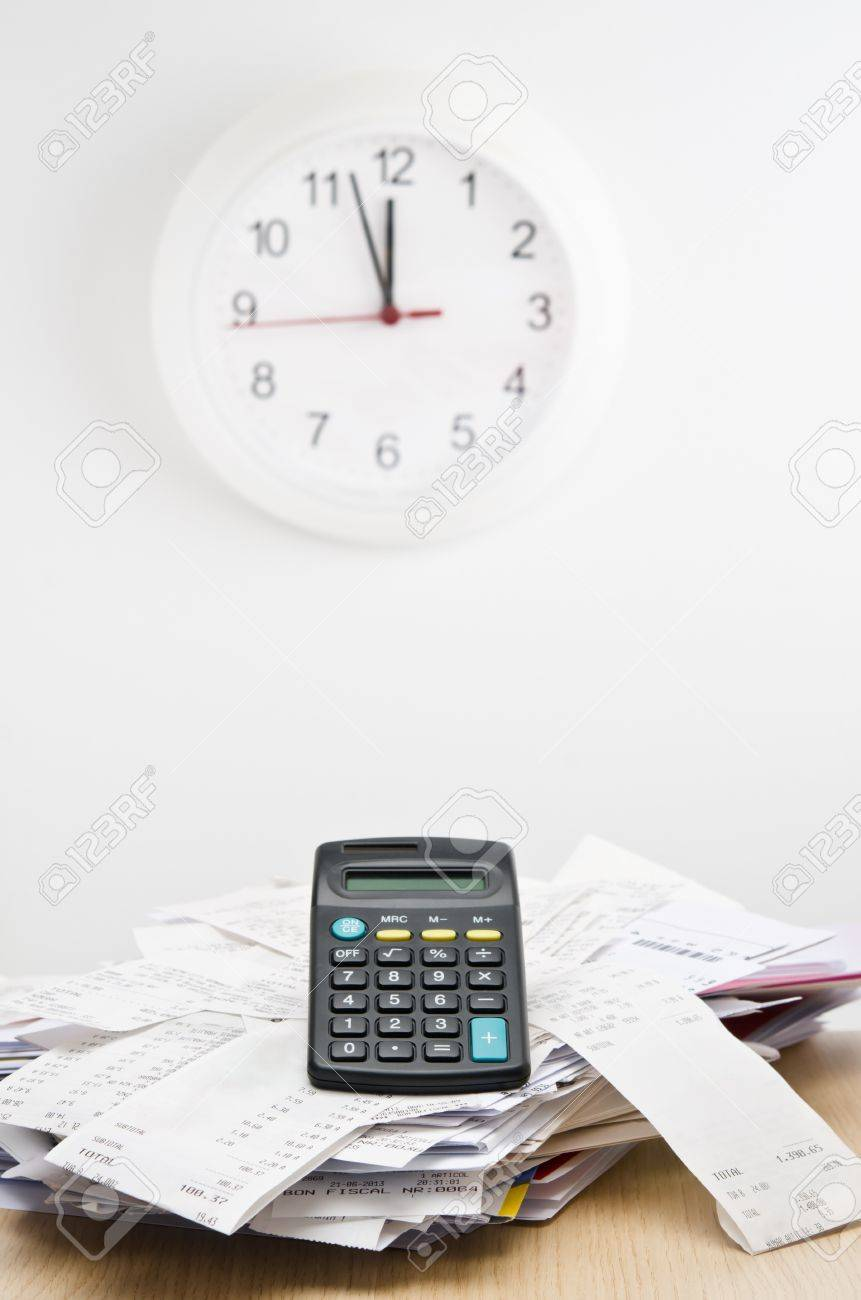 tax time calculator on top of a stack of bills with a clock stock