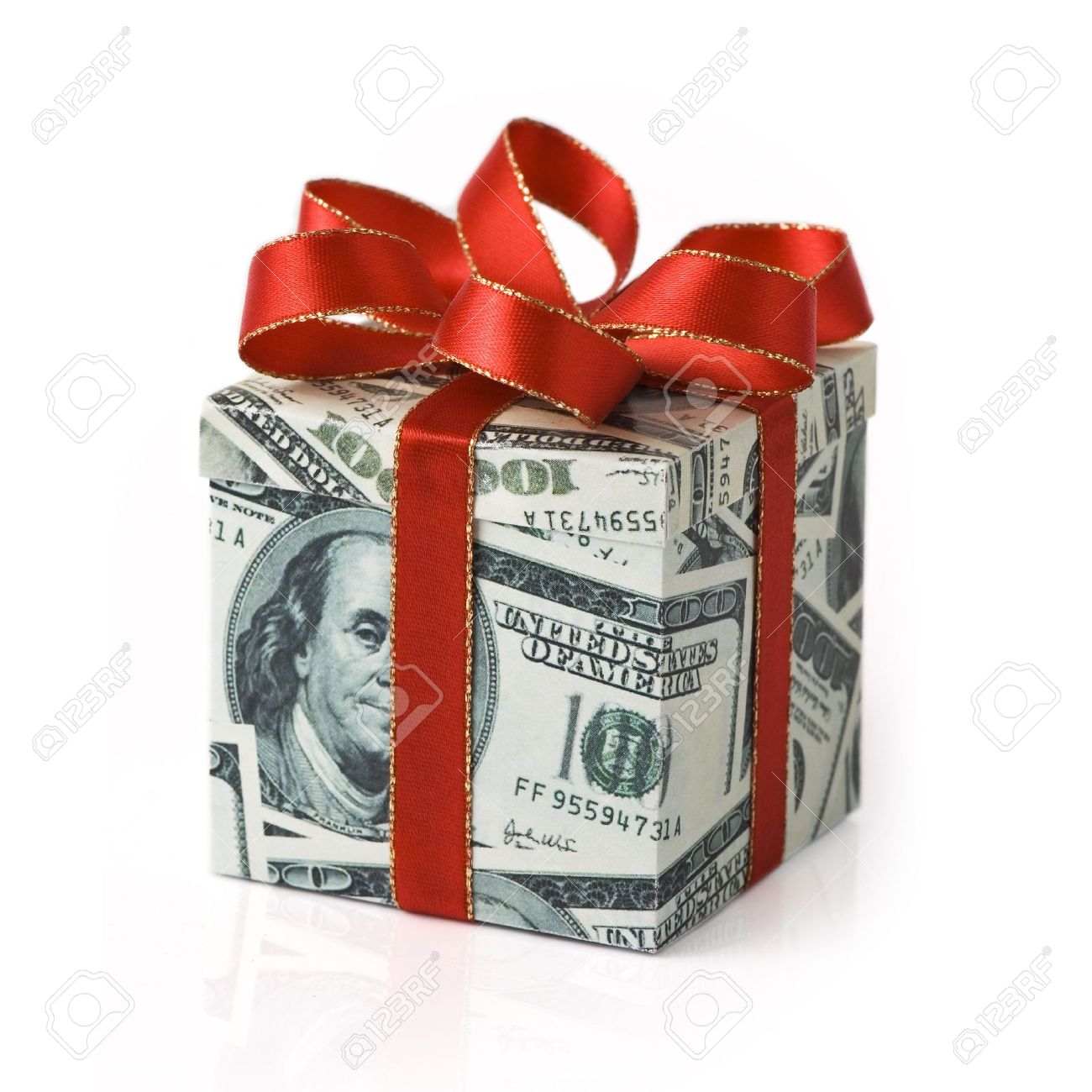 A gift box covered in US money with red colored ribbon applied Stock Photo - 20902642