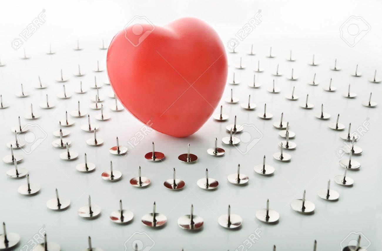 Heart surrounded by thumbtacks symbolizing solitude Stock Photo - 20902610