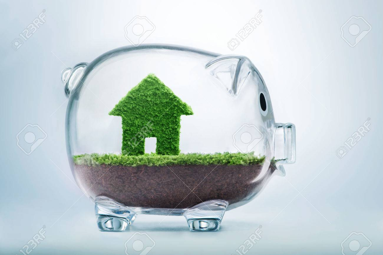 Saving to buy a house or home savings concept with grass growing in shape of house inside transparent piggy bank - 52519479