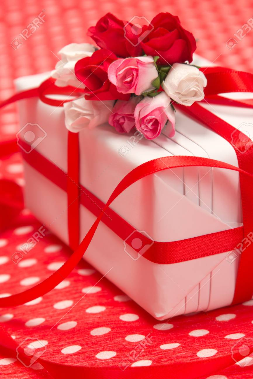 White Gift Box With Red Bow And Paper Flowers On Red Background ...