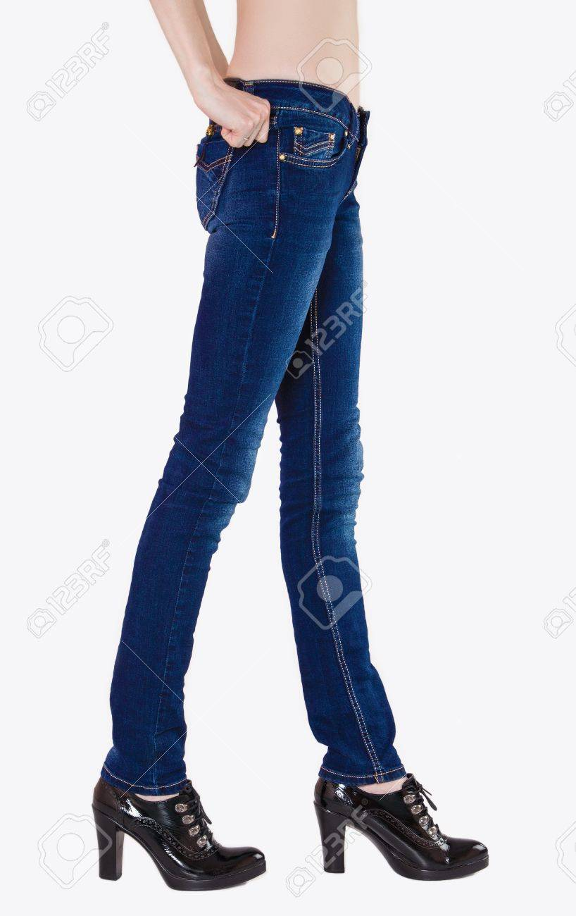 2da57be86d Shapely female legs dressed in dark blue jeans and black varnished boots  with high heels Stock
