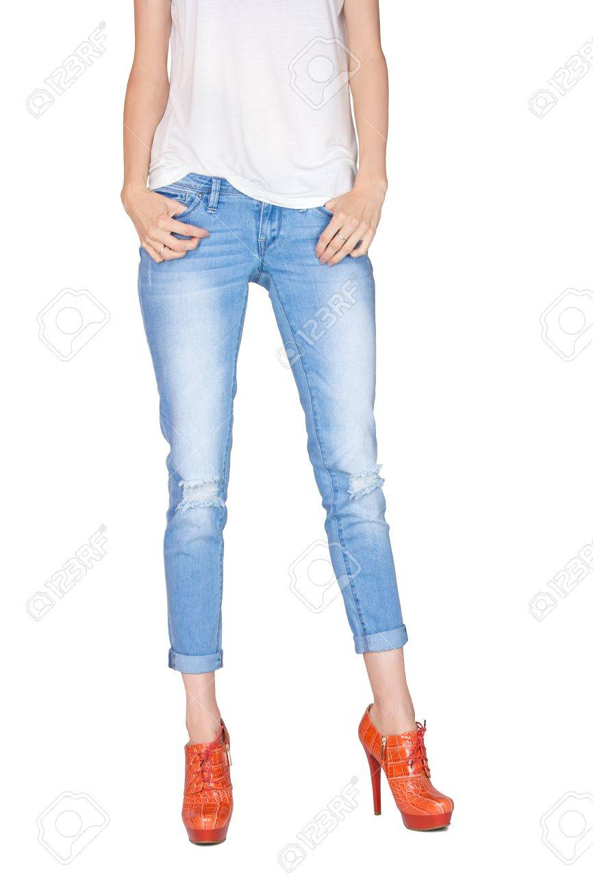 d6d32ae1c1 Shapely female legs dressed in stylish blue jeans and orange boots with  high heels on white