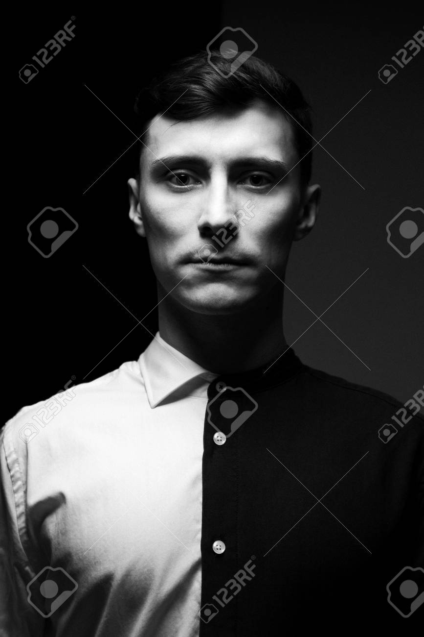 Low key portrait of a man in different shirts in black and white stock photo
