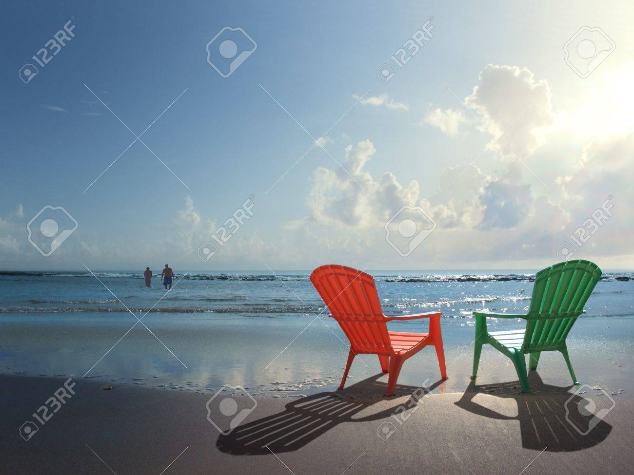 Two colorful Adirondack chairs at the beach and a couple in a..