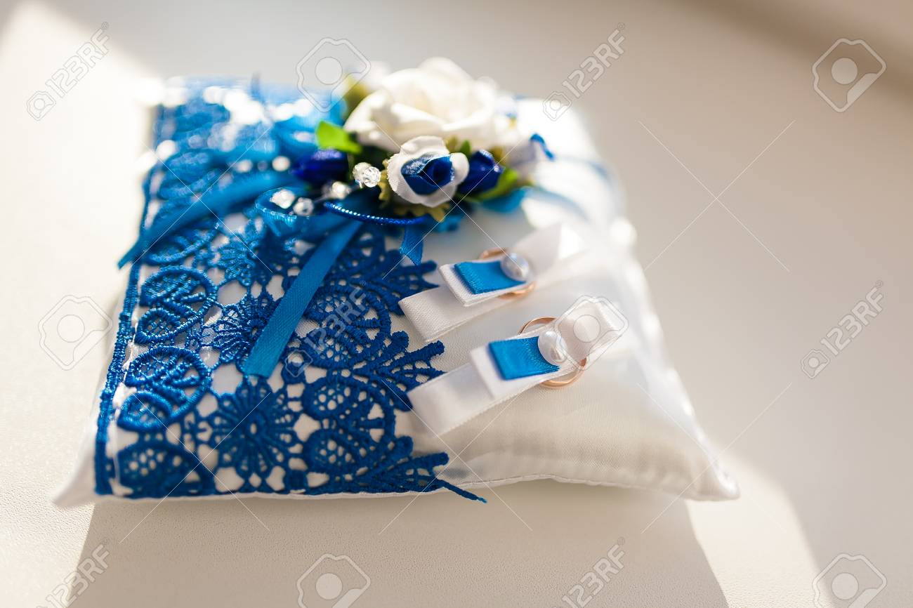 Wedding Rings On A Blue And White Decorative Pad Wedding Decorations
