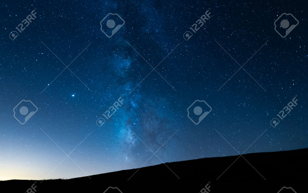 Milky way up a hill in a starry night sky. Blue sky with stars without light pollution. - 157794700