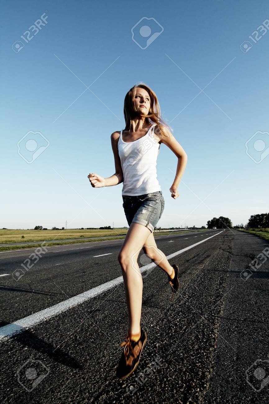 The woman running on road against the sunset sun Stock Photo - 5191384
