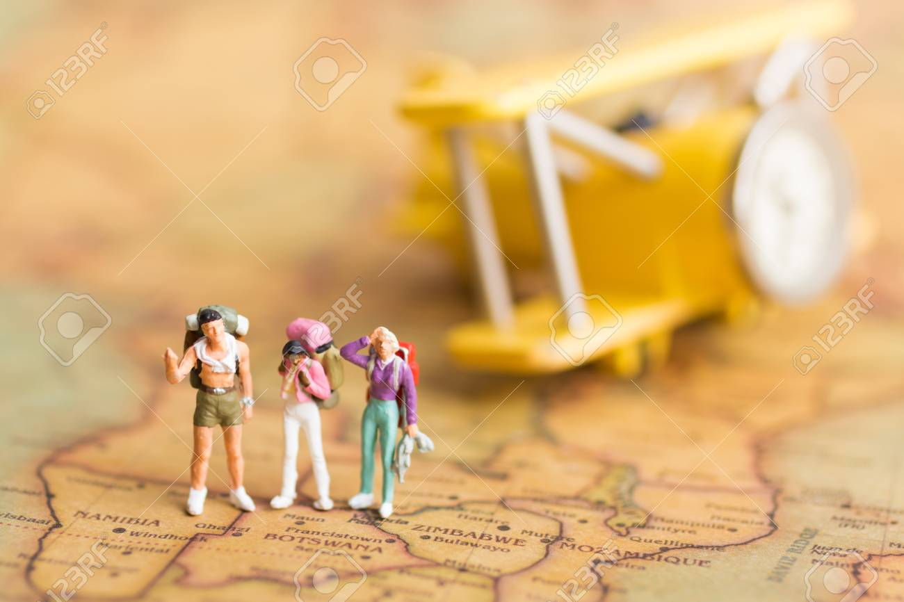 Miniature people travelers with backpack standing on world map miniature people travelers with backpack standing on world map travel by plane used as a gumiabroncs Images