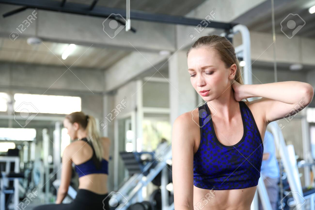 Young women are experiencing muscle aches from excessive exercise. - 143799917
