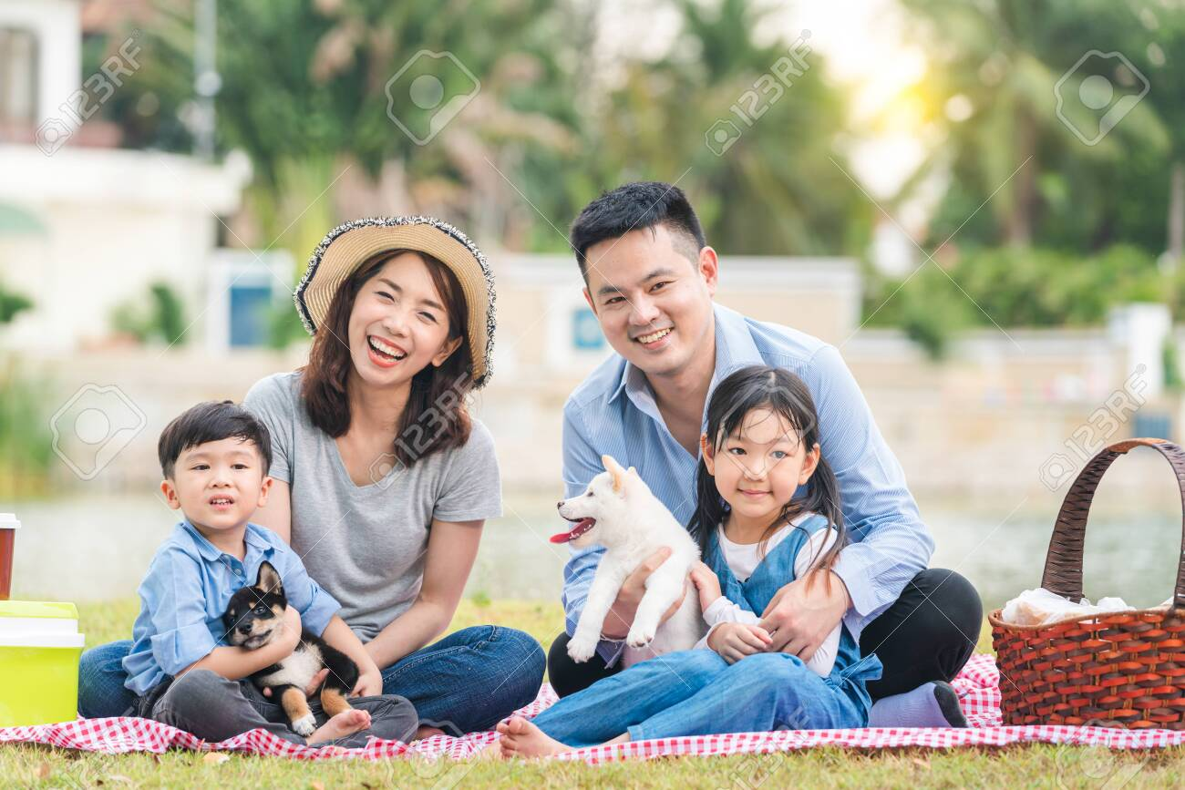 An Asian family plays with a Shiba Inu dog. Family has father, mother and son, daughter. Picnicking in the garden. - 150447873