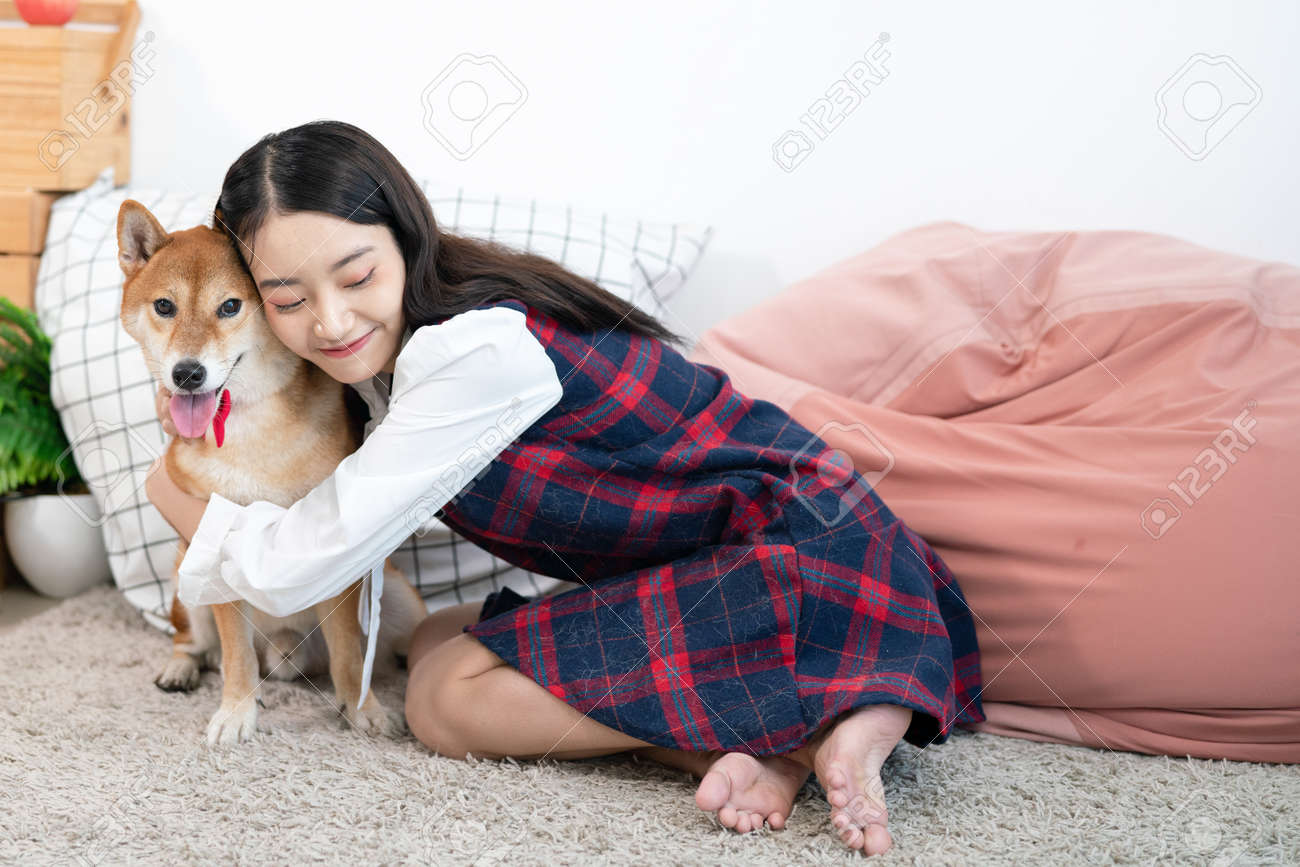 An Asian woman lovingly hugs the Shiba Inu. Dog and girl in the living room. - 160756484