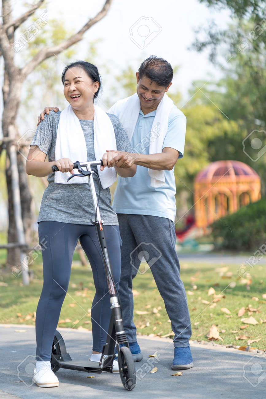 An elderly couple is teaching his wife to play a scooter. Sporty mature couple staying fit with sport. - 169476291