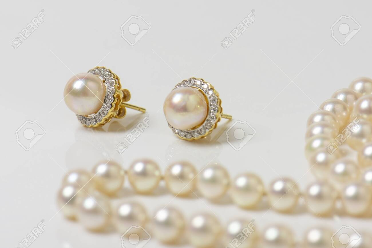 Pair of natural pearl earrings on white with pearl necklace in the background. - 148424030