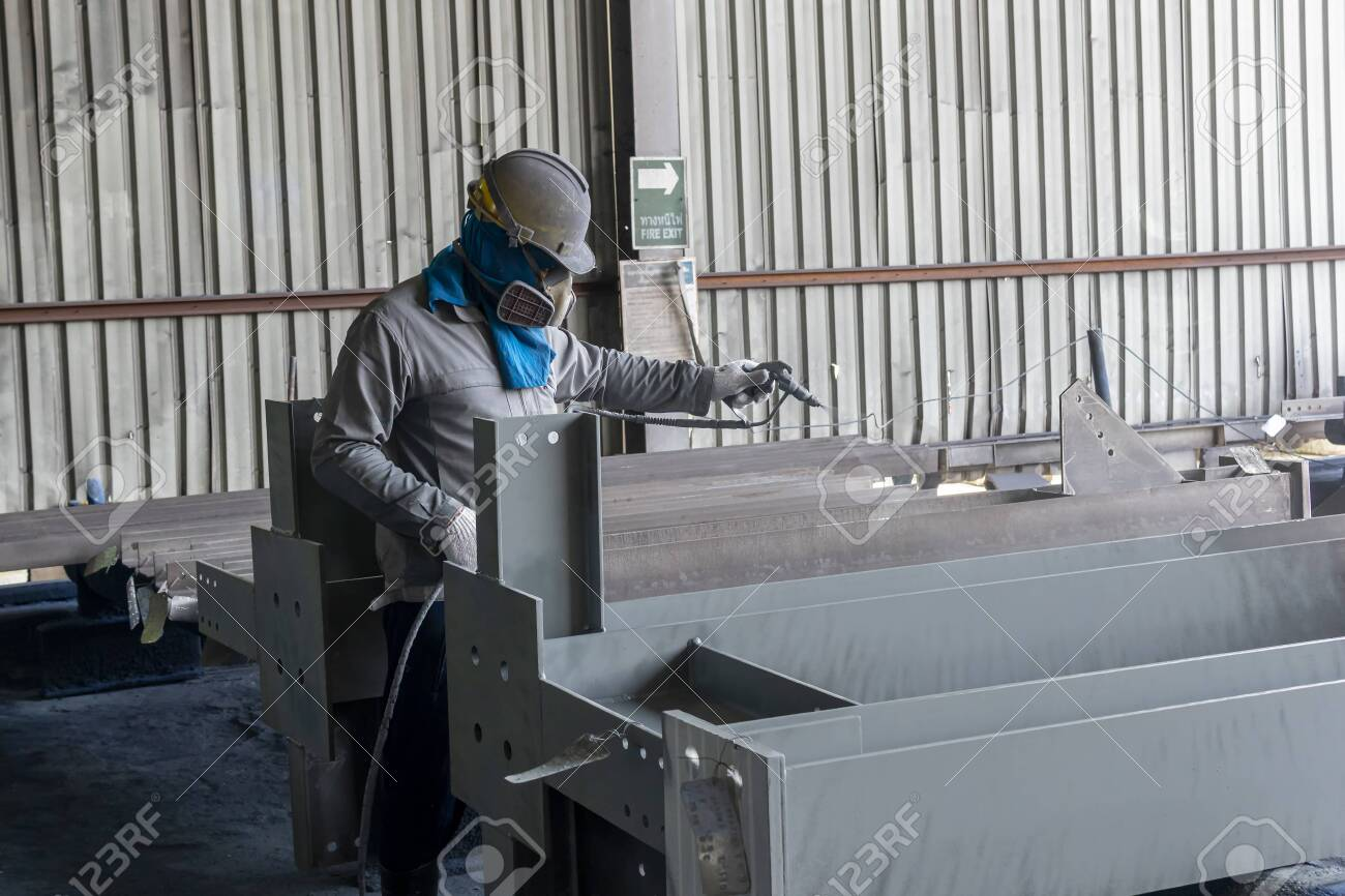 The painter is working to painting the steel structure with spray gun at industrial factory. - 146472094