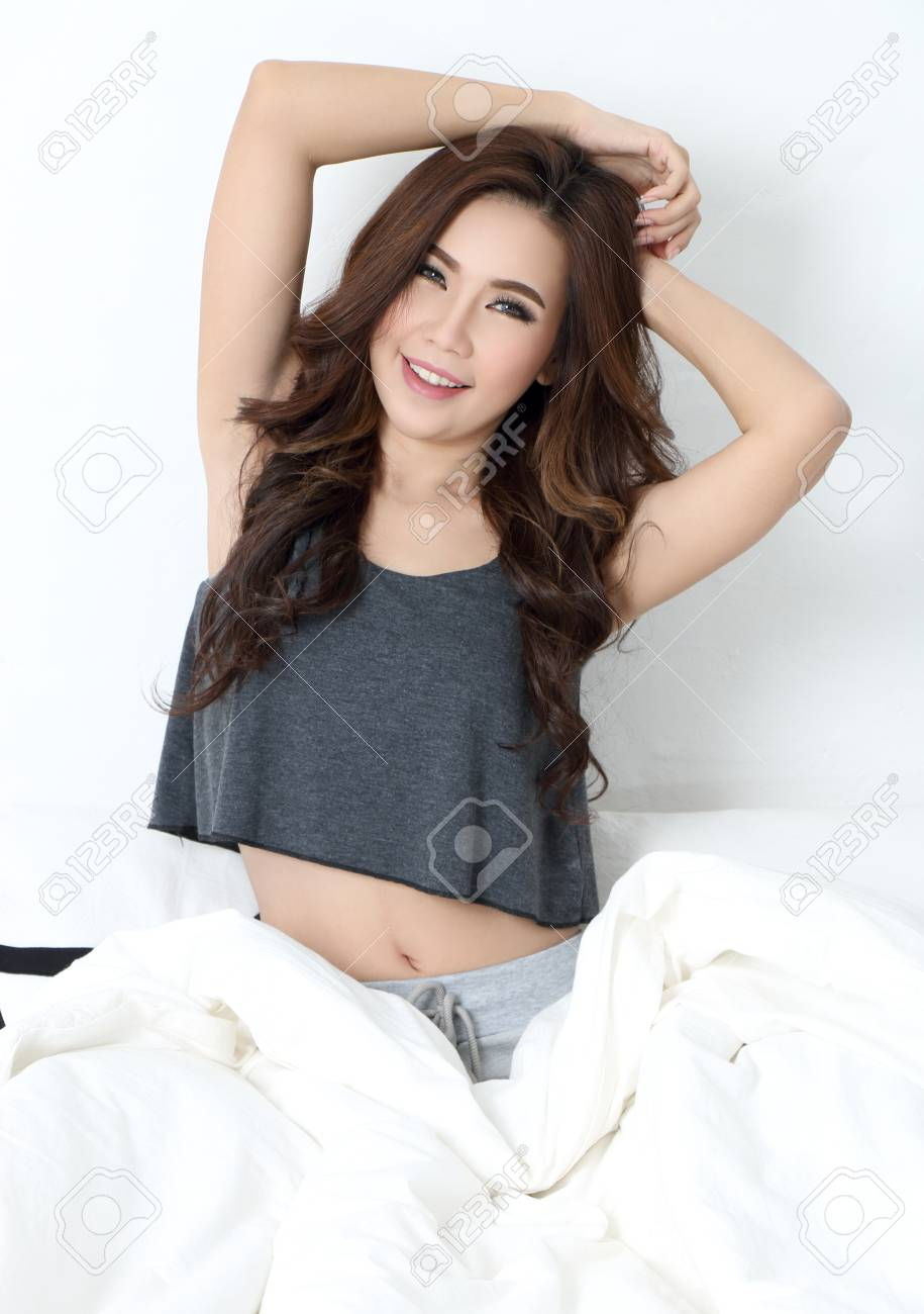 young beautiful asian woman sleepy on the bed Stock Photo - 79025073