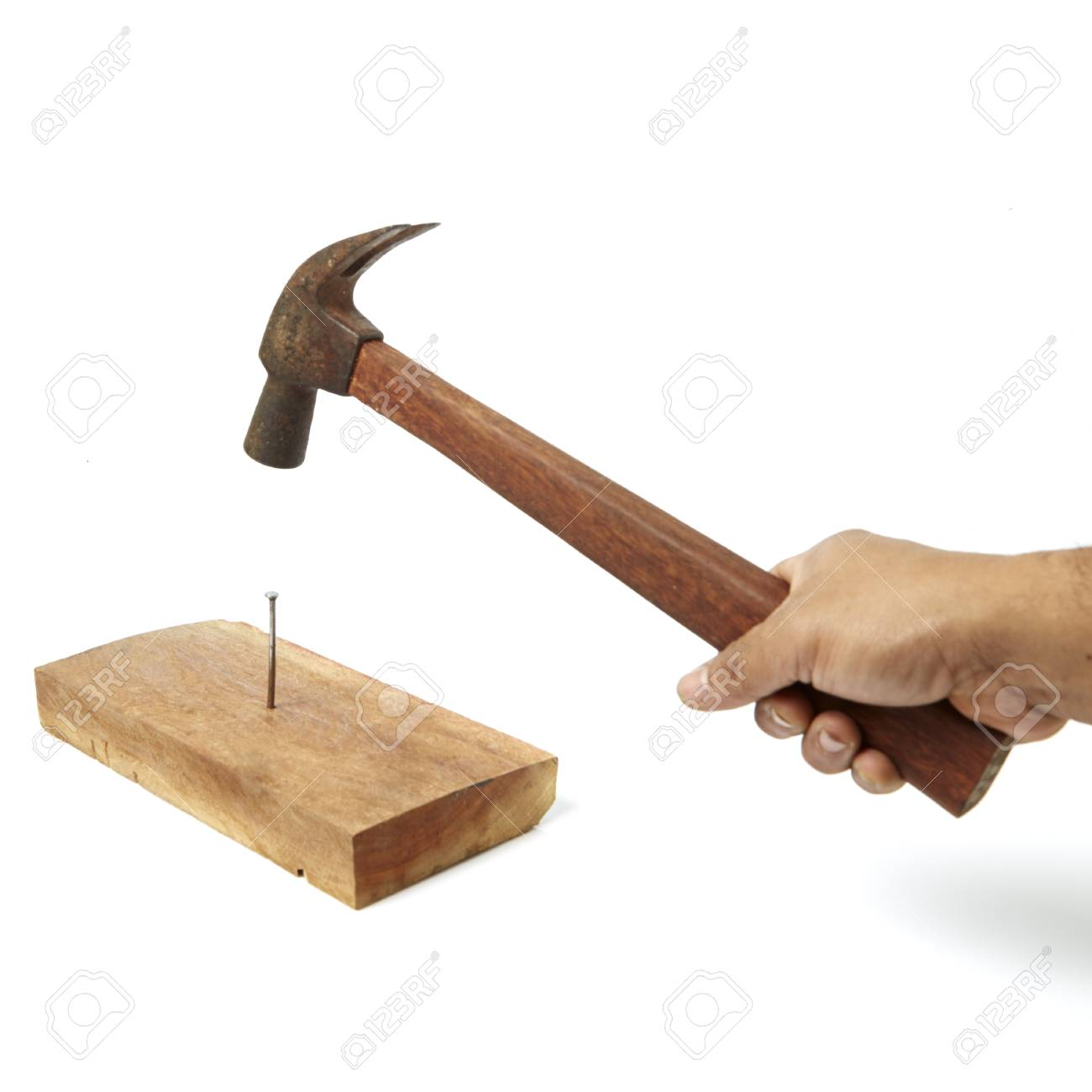 Hammer Pounding A Nail In A Wooden Board Stock Photo Picture And