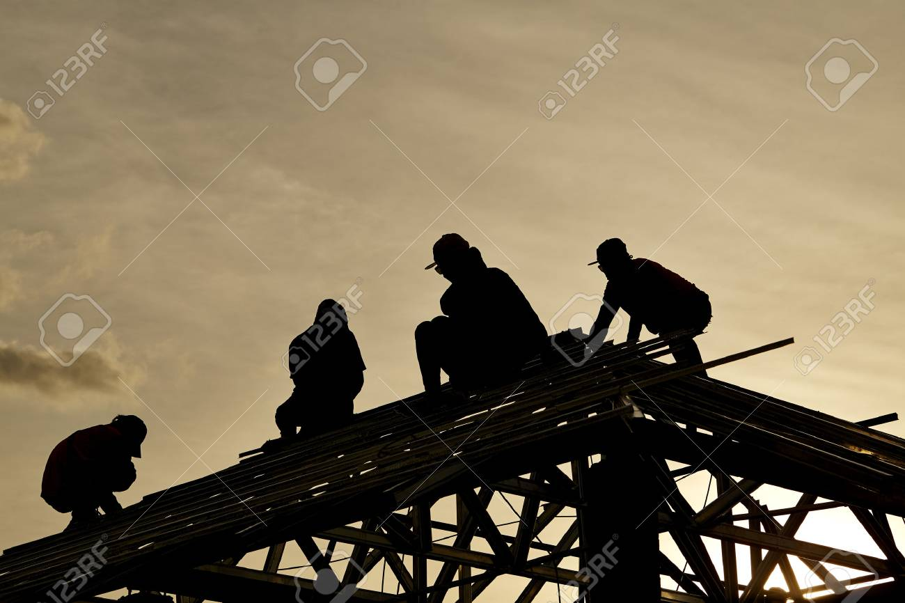 Contractor in Silhouette working on a Roof Top with Sky in background - 84076692