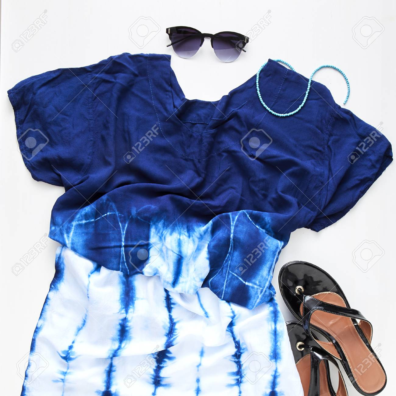 88affea8002a flat lay feminine clothes and accessories collage with jean, sunglasses,  earring White wood table