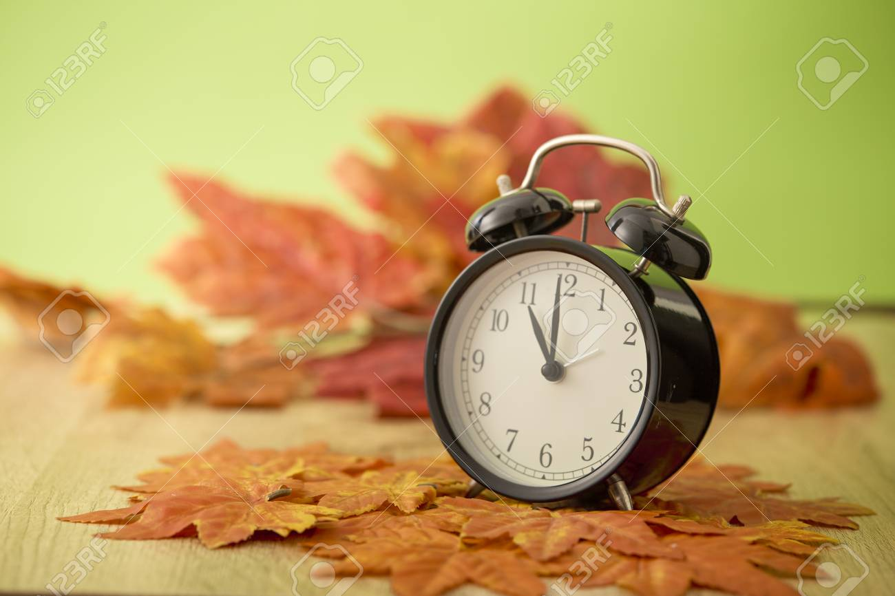 Black vintage clock with dried maple leaves on green background - 108149674