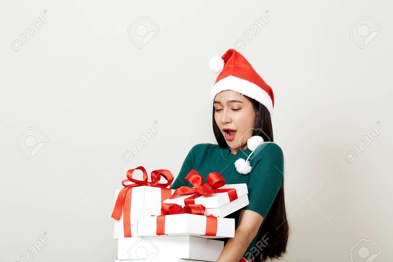 Beautiful Asian woman in in santa hat with many gifts studio shot isolated on bright gray background, copy space for text, Christmas Concept and new year - 134721750