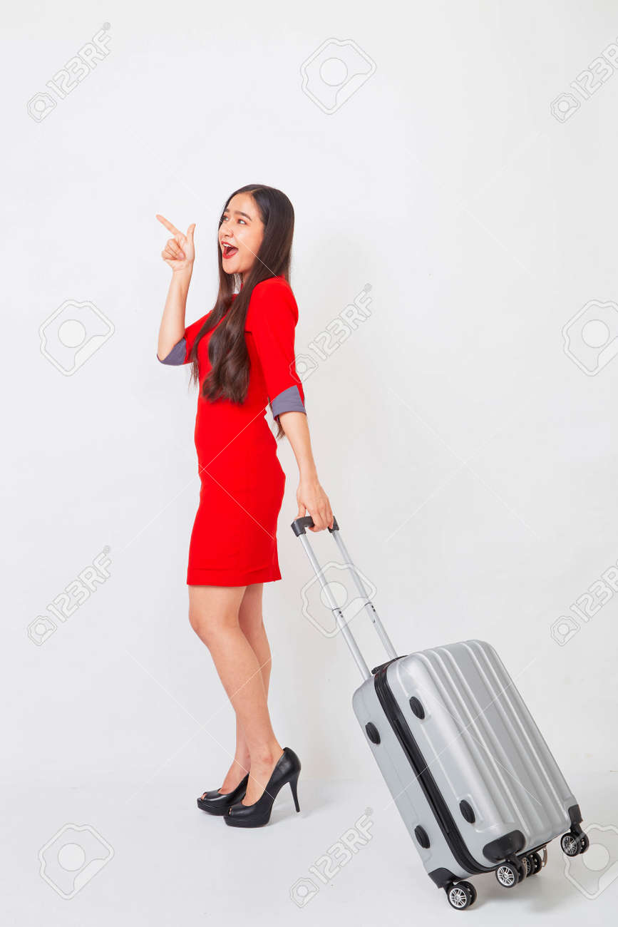 A businesswoman in a red dress with a suitcase on white background, travel concept - 152642053