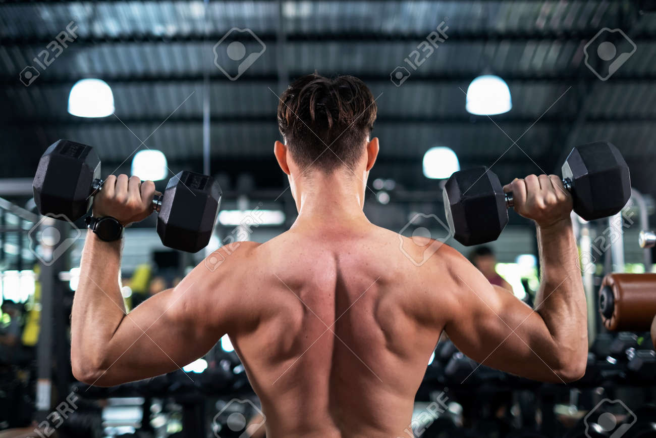 Back view of attractive portrait man lifting dumbbells with both hands in the sport fitness gym. Weight training muscles. Show body muscle biceps, triceps. Healthy lifestyle and exercise concept. - 166966215