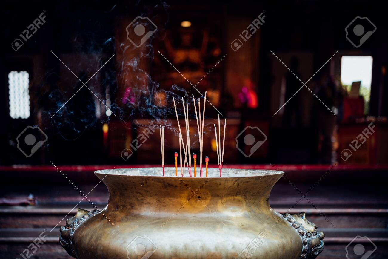 Joss stick or incense sticks burning by fire with smoke for buddhist