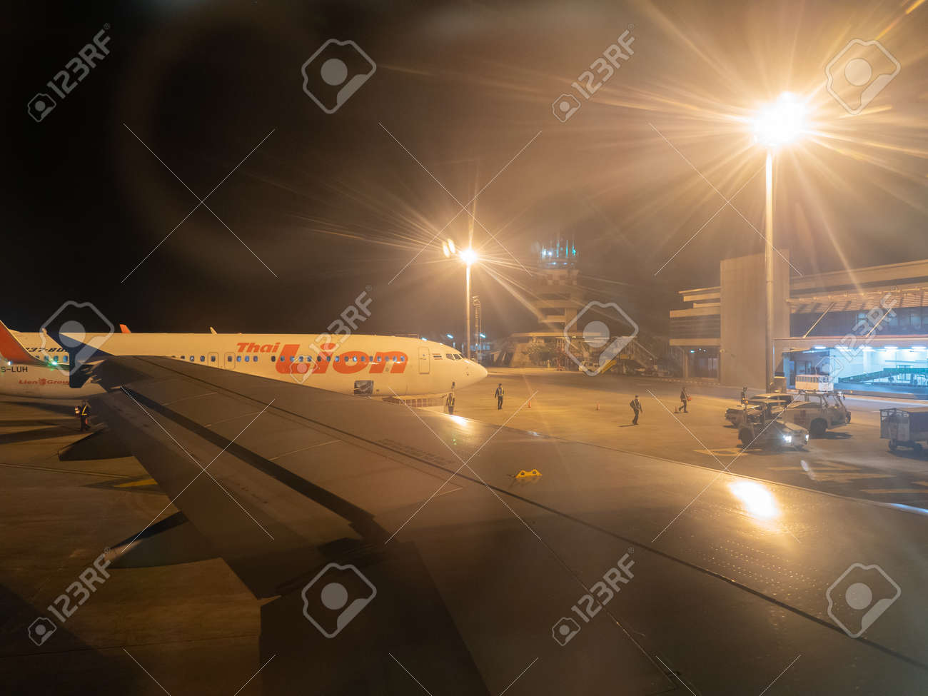 Udon Thani, Thailand - 17 Desember, 2017: Airplane parking on Udon Thani International Airport, Thailand, Thai Lion Airlines and the Fair Light of the High Light Pillar at the airport at night. - 129934539