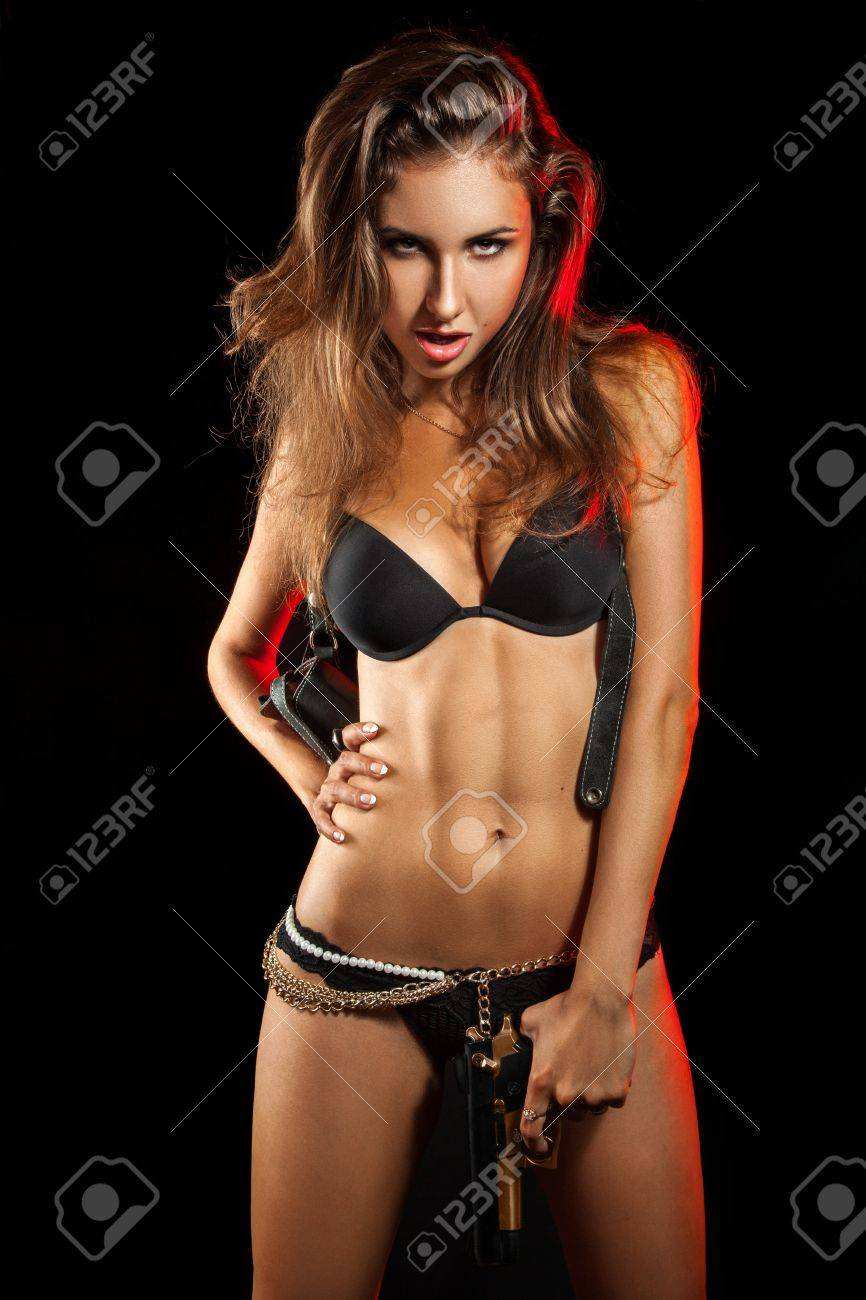 Hot woman with gun in studio on black background Stock Photo - 20486270
