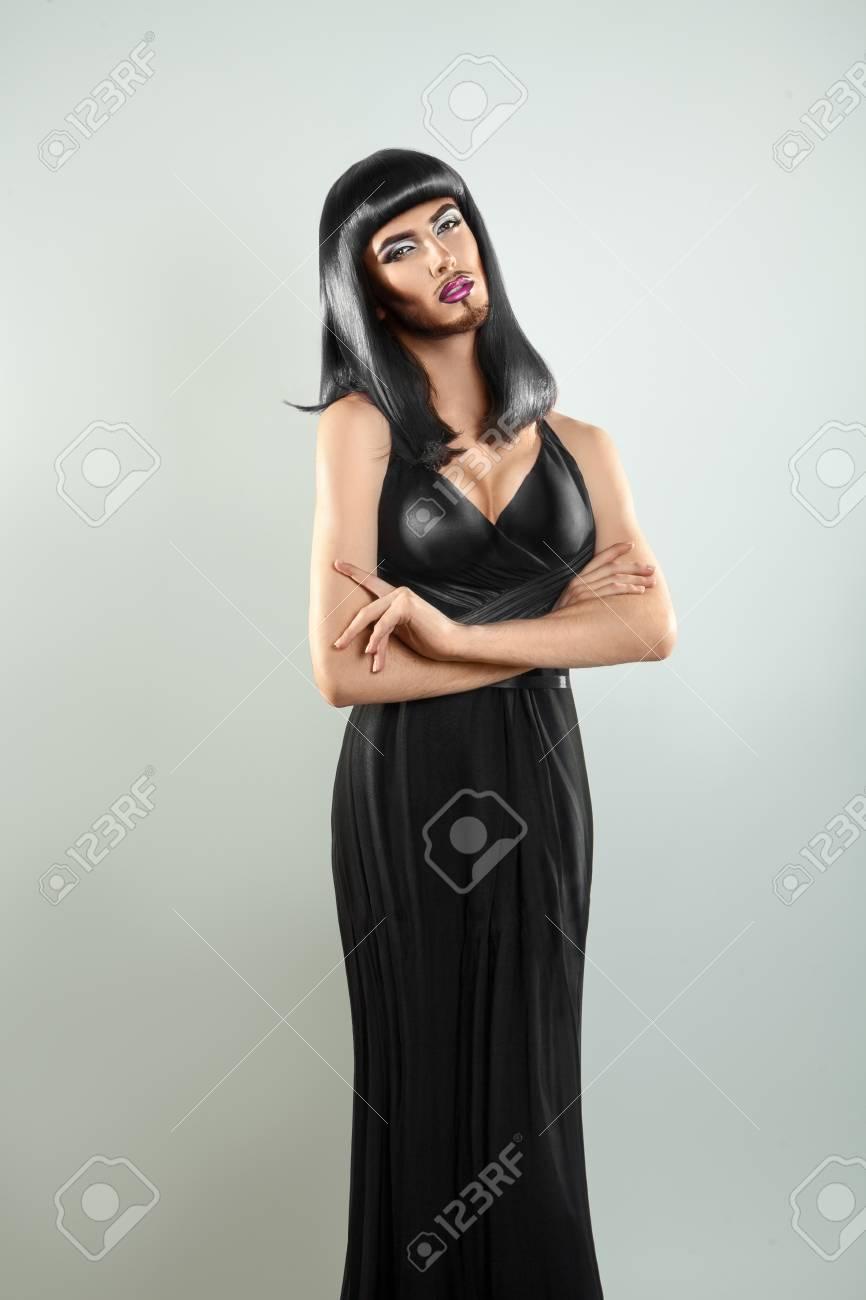 b787f1335d Brunette shemale model in black dress and nice makeup. Studio shot. Gray  background.