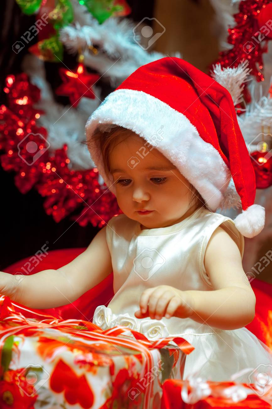 baby girl opens her first christmas gift stock photo 47982099