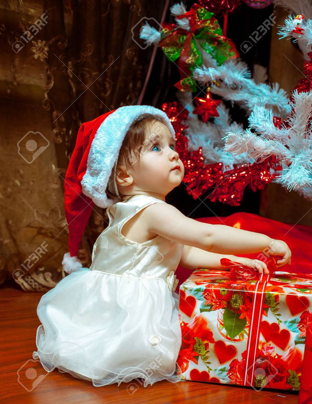 cute little baby girl in santa hat opens her first christmas present stock photo