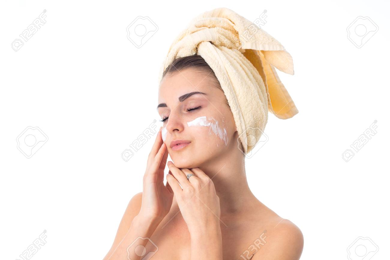 lovely girl takes care her skin with towel on head smeared with