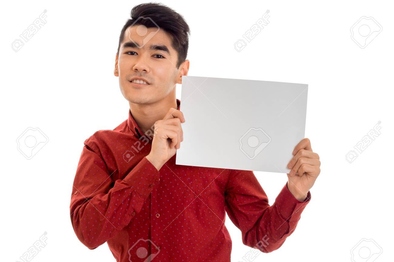 6741ce1e985b8 Foto de archivo - Retrato de hombre joven con estilo en camiseta roja con  cartel vacío en sus manos aisladas en blanco