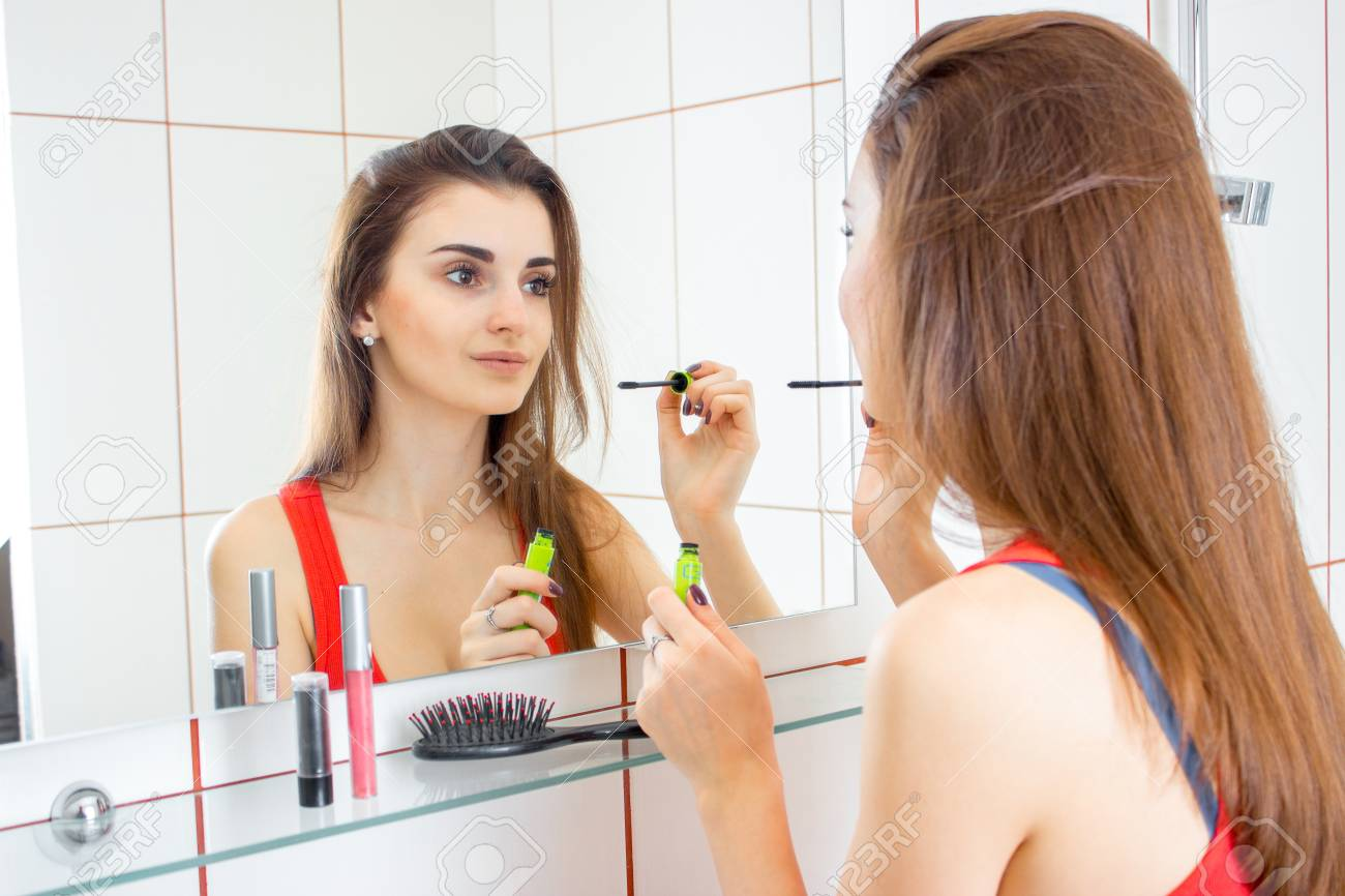 Cute Young Girl Stands In Front Of The Mirror In The Bathroom