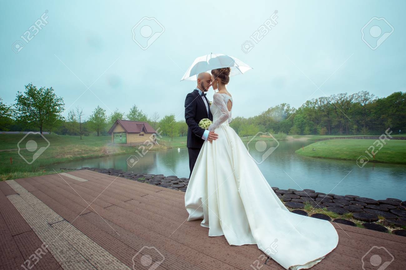 Lovely Young Just Merried Couple In Wedding Suits Hugging Under ...