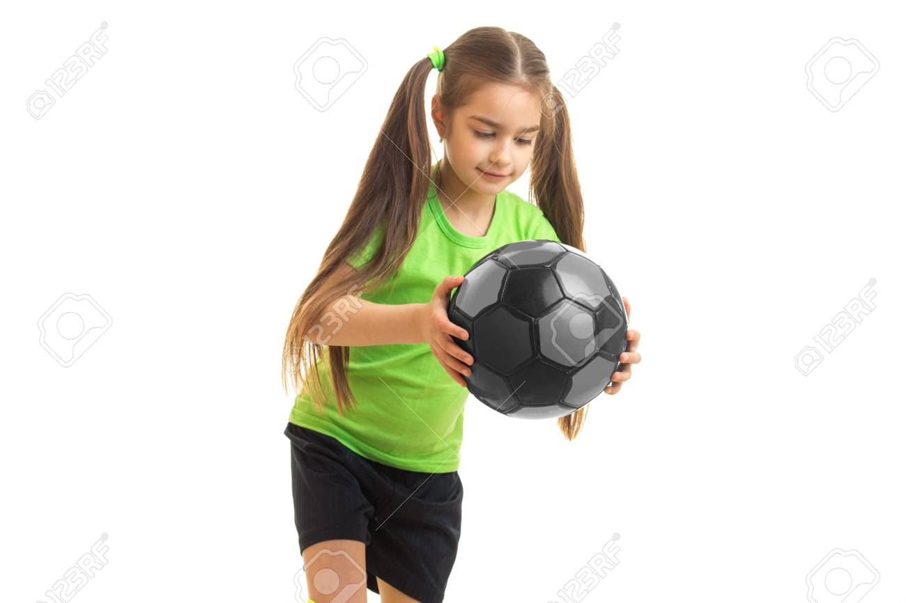 432b0d0a2 cutie little girl in green uniform with soccer ball in hands isolated on  white background Stock