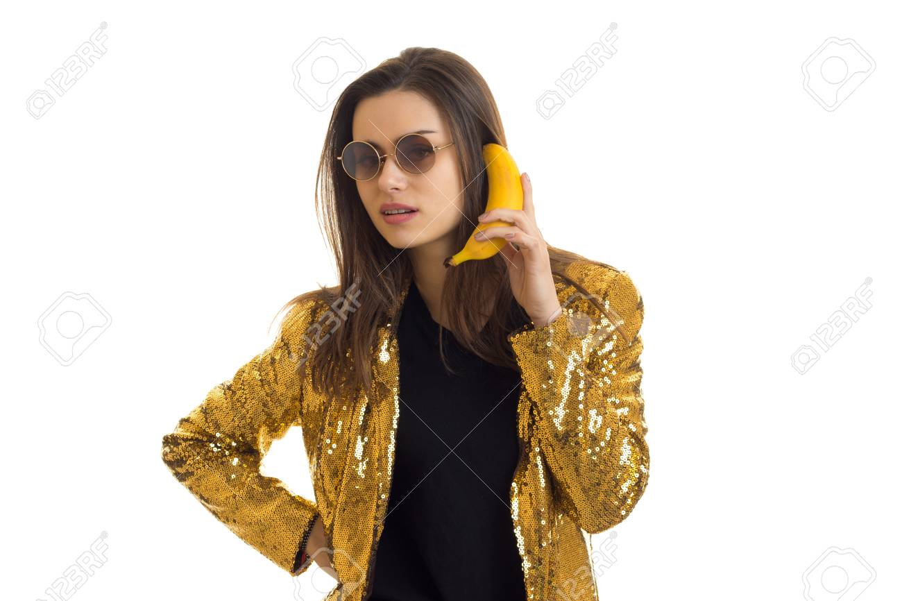 60a97ea88c Stock Photo - young brunette in a stylish round glasses and a gold jacket  keeps banana near ear isolated on white background