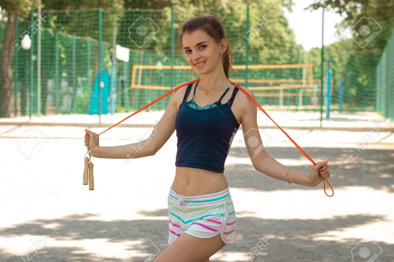 Beautiful Skinny Girl Looks Into The Camera Smiling And Holding A Rope Stock Photo