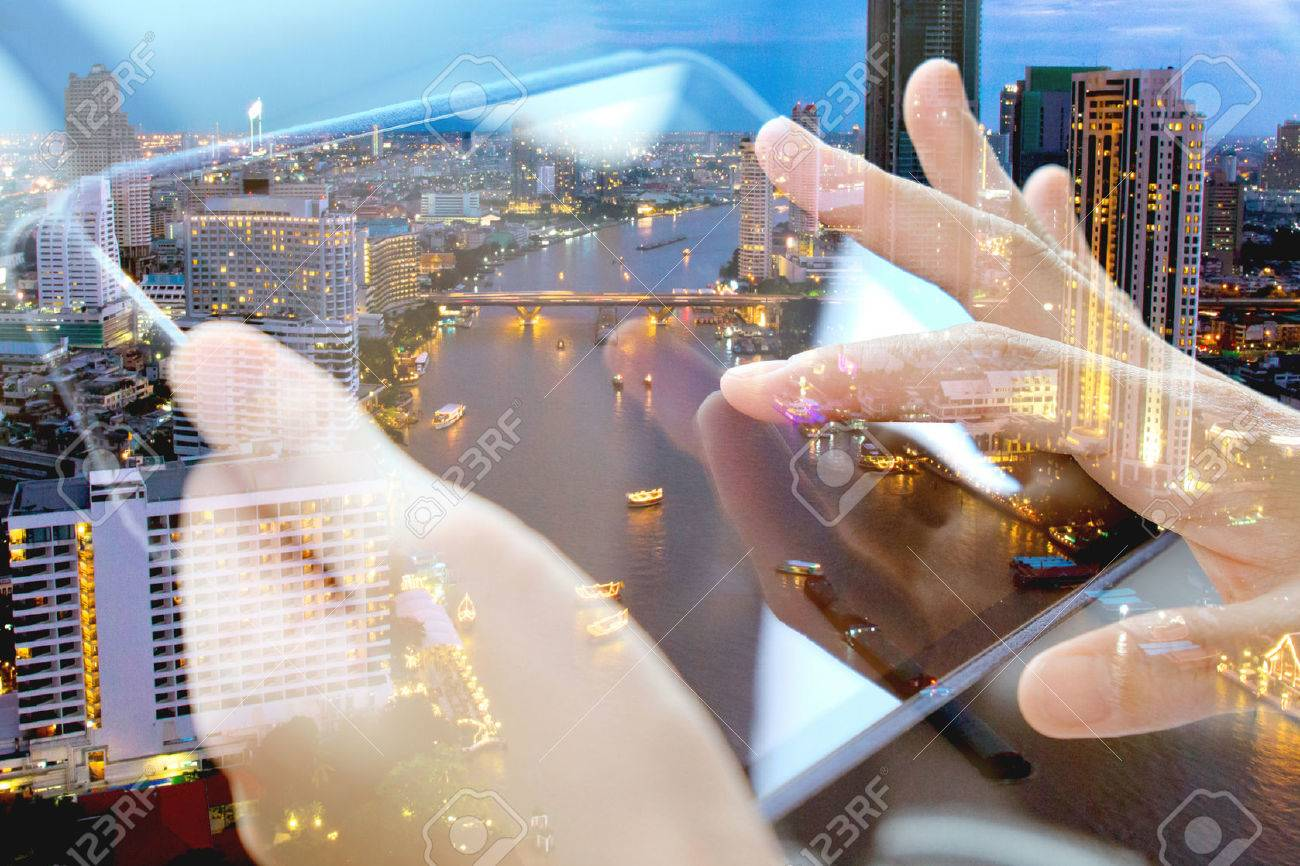 Using digital tablet double exposure and and cityscape background. Business technology concept. Stock Photo - 47600645