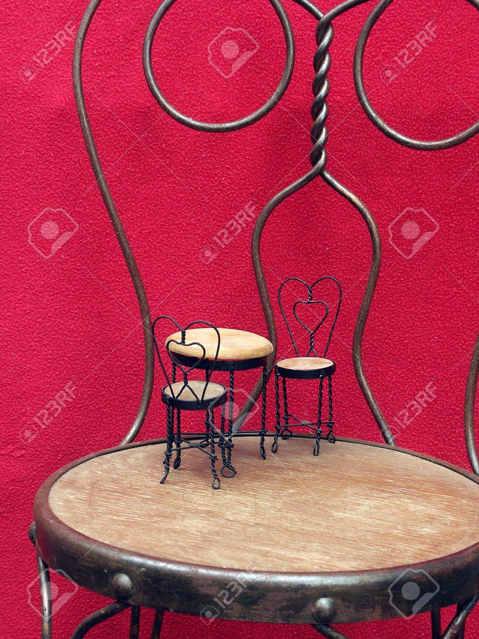 Miniature Ice Cream Table And Chairs Sitting On Full Sized Ice Cream Chair  Before Red Background