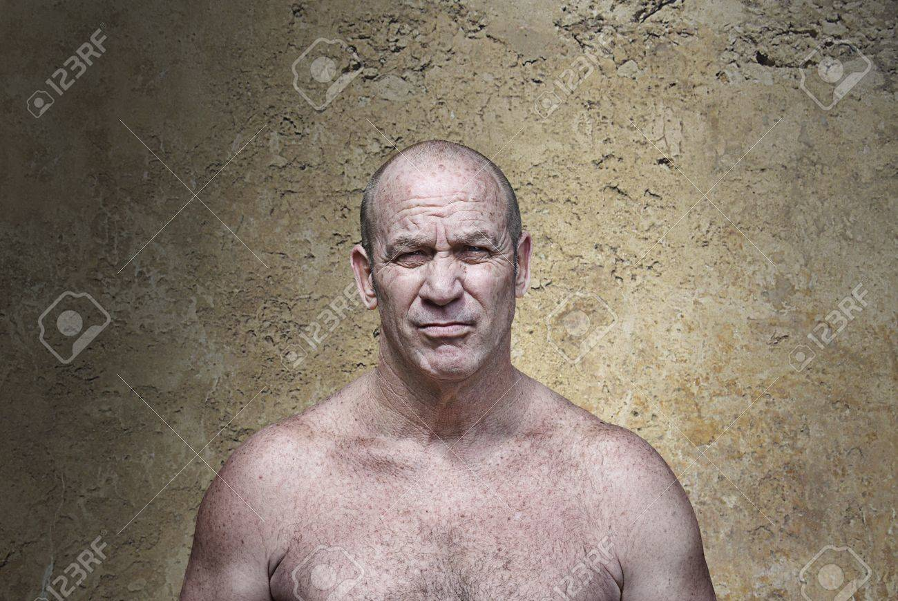 Muscular scowling man in aggressive posture in front of a concrete wall Stock Photo - 13733782