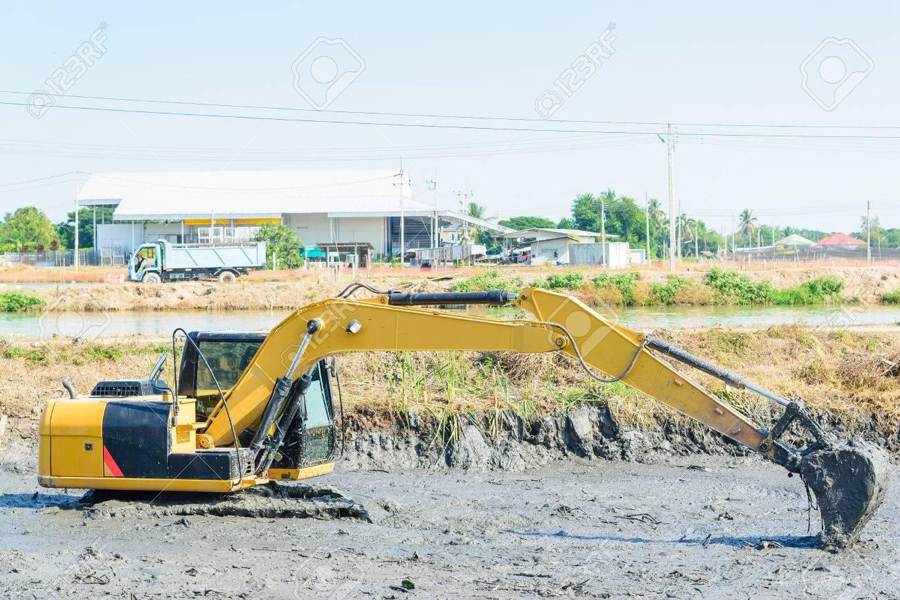 Backhoe working in mud swamp, digging mud