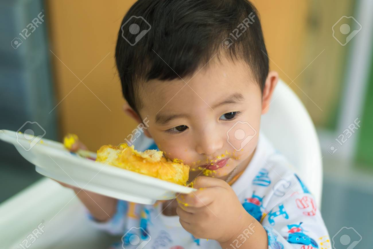Asian Kid Eating Birthday Cake With Cream On Face At Home Shallow