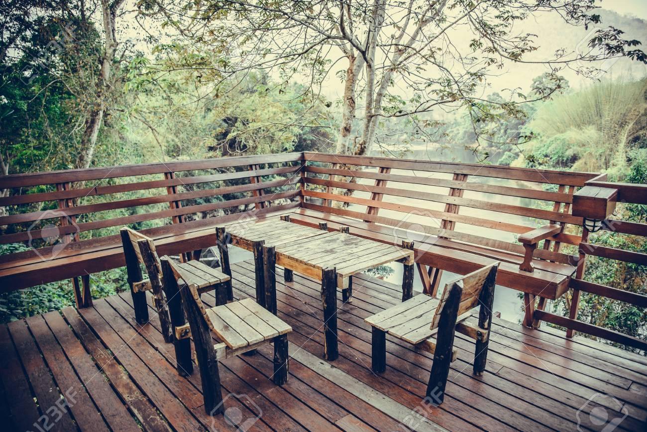 Mesa Y Silla De Madera En El Recurso Y El Jardín Cenando Fijaron En La Terraza De Madera En Restaurante Tono De La Vendimia Con El Vignetting