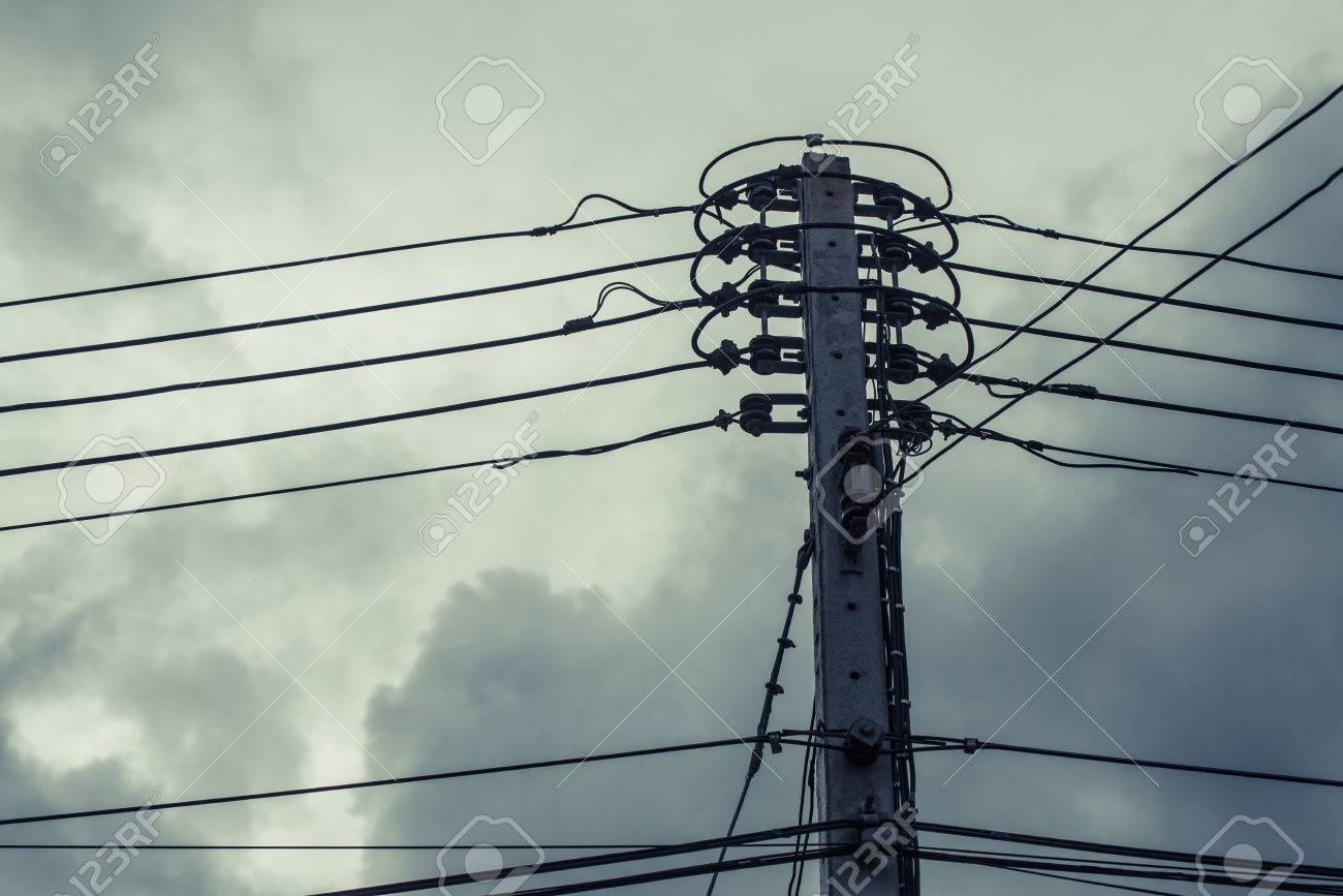 High Voltage Power Pole With Wires Tangled On Building Background ...