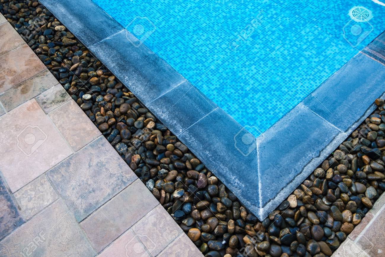 Edge of swimming pool with blue mosaic tiles at the bottom of..