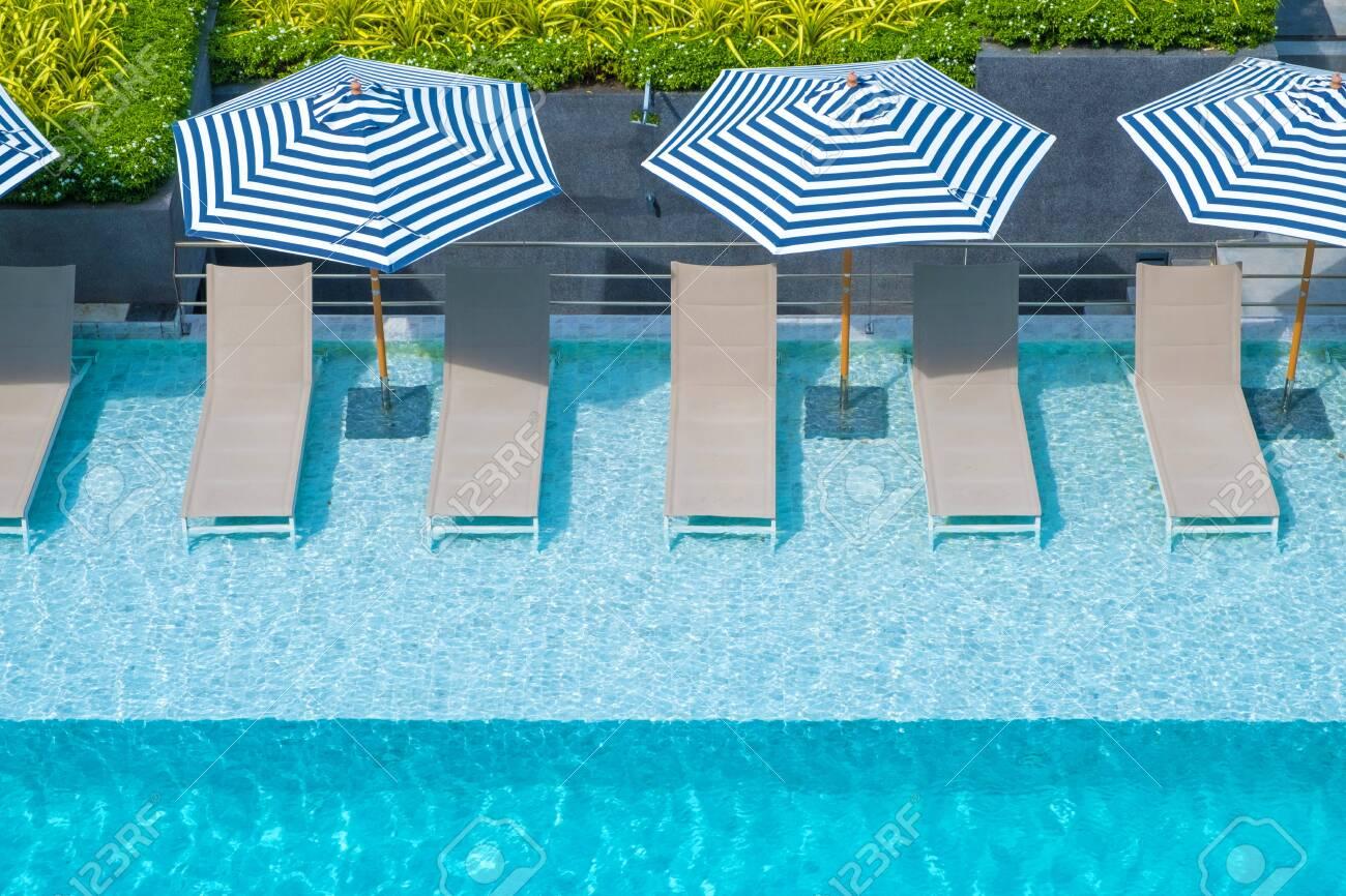 Deck Chair Or Sunbath Near Private Swimming Pool With Sun Umbrella
