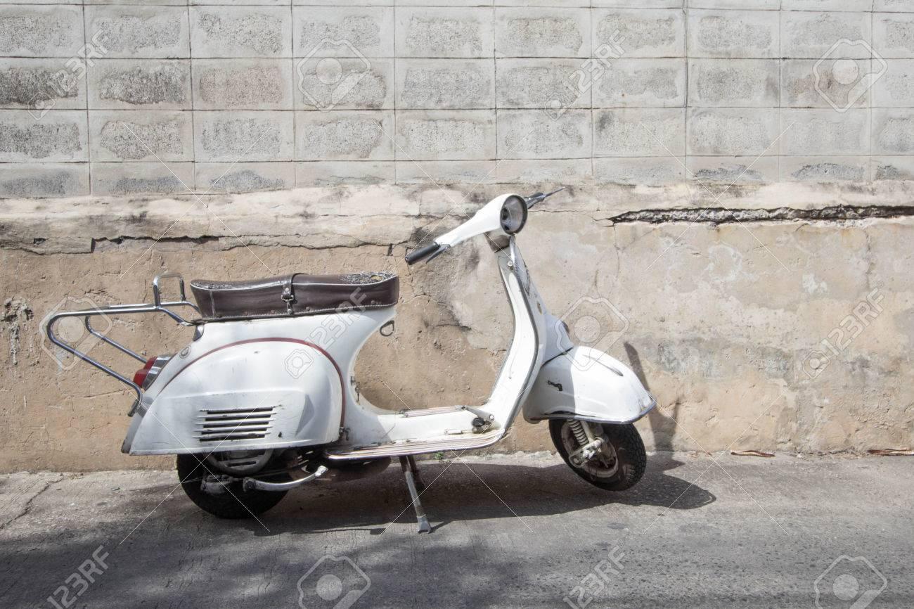Ancien Scooter blanc scooter vespa classique se stationne près du vieux mur de